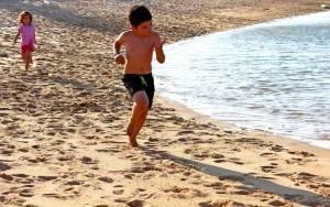 A little boy and a little girl running on the beach